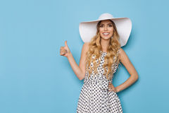Elegant Fashion Model In Summer Dress And Sun Hat Is Showing Thumb Up And Smiling stock photography