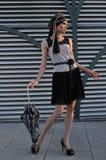 Elegant fashion model wearing designers clothes and holding umbrella Royalty Free Stock Photography