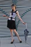 Elegant fashion model wearing designers clothes and holding umbrella Royalty Free Stock Images