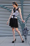 Elegant fashion model wearing designers clothes and holding umbrella Stock Image