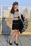 Elegant fashion model wearing designers clothes and holding umbrella Stock Photos