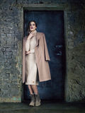 Elegant fashion model wearing long mocha coat, posing before a door. Royalty Free Stock Image