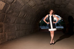 Elegant Fashion in Urban Underpass. Beautiful young lady standing in underpass with city park in background Royalty Free Stock Photos