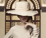 Elegant fashion woman. Cute fashion shot of elegant woman with face covered by big hat, wearing beige dress Royalty Free Stock Photo