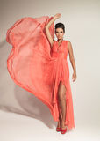 Elegant fashion woman fluttering her coral dress Royalty Free Stock Photography