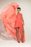 Elegant fashion woman fluttering her coral gown Royalty Free Stock Images