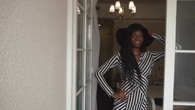 Elegant fashionable african american woman in black hat and striped dress posing at her luxury apartments.  stock video footage