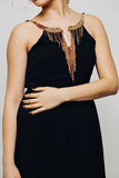 Elegant fashionable black dress with gold jewelry on a beautiful young blonde girl fashion model with curly long blond Stock Image