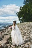 Elegant and fashionable brunette plus-size model girl in the stylish lace wedding dress with stylish hairstyle and with royalty free stock photography