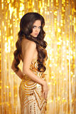 Elegant fashionable woman in golden dress over Christmas party l. Ights bokeh background. Beautiful brunette girl with long healthy wavy hair style posing in Stock Image