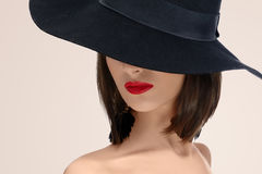 Elegant fashionable woman posing wearing a hat in studio. Close up studio portrait of a red lipped woman posing in a hat covering her face mystery mysterious Stock Image