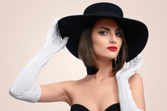 Elegant fashionable woman posing wearing a hat in studio Royalty Free Stock Photography