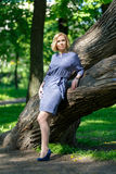 Elegant fashionable young woman standing near big tree Royalty Free Stock Images