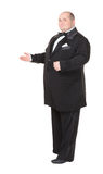 Elegant fat man in a bow tie pointing. Elegant fat man in a dinner jacket and bow tie smiling charmingly as he holds out his hand to the side gesturing in that Royalty Free Stock Image