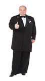 Elegant fat man in a tuxedo shows thumb-up. Elegant very fat man in a tuxedo and bow tie shows thumb-up, on white background Stock Photos