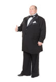 Elegant fat man in a tuxedo shows thumb-up. Elegant very fat man in a tuxedo and bow tie shows thumb-up, on white background Stock Image