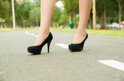 Elegant feet wearing black high heels walking on Royalty Free Stock Photography
