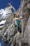 Elegant female alpine climber ascents natural rock Royalty Free Stock Photos