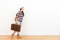 Elegant female backpacker carrying retro suitcase. Beauty elegant female backpacker carrying retro suitcase walking on wooden floor ready to travel and looking Stock Image