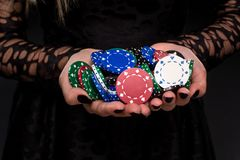 Elegant female casino player holding a handful of chips on black background, hands close up Stock Photo