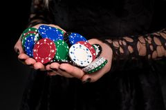 Elegant female casino player holding a handful of chips on black background, hands close up Royalty Free Stock Images