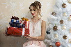 Elegant female in christmas day. Elegant woman in interior xmas portrait sitting near decorated tree with some christmas presents in the hands and looking them royalty free stock image