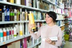 Elegant female customer buying conditioner for hair Stock Photos