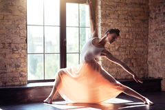 Elegant female dancer moving gracefully. In action. Serious charming young lady bending to the left and stretching out her arms while dancing Stock Image