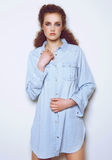 Elegant female fashion model posing in denim shirt. Portrait of an elegant female fashion model posing in denim shirt royalty free stock photo