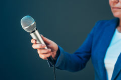Elegant female journalist conducting business interview. Hand with microphone Royalty Free Stock Photos