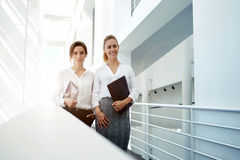 Elegant female lawyers holding touch pad and folder while standing in office interior after successful meeting, Royalty Free Stock Image
