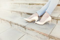 Elegant female legs in blue jeans and beige lacquer shoes on sta Stock Photography