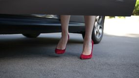 Elegant female legs in red heels getting into car stock video footage