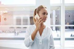 Elegant female proud coe having serious telephone conversation  Royalty Free Stock Photo
