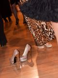 Elegant female shoes in a dance hall with people Royalty Free Stock Photo