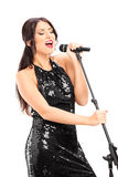 Elegant female singer singing on microphone Stock Photo