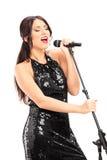 Elegant female singer singing on microphone Stock Photo