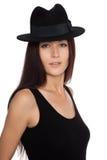 Elegant flicka i en svart filthatt arkivfoto