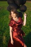 Elegant flicka i röd klänning med svarta ballonger arkivbilder