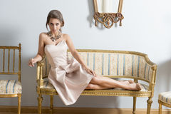 Elegant flicka som ligger på tappningsoffan arkivfoton