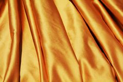 Elegant folds, background. Golden soft elegant folds of fabric as a background, pointing out the preciousness of the texture Stock Photo