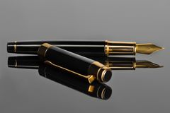 Elegant Fountain Pen on a Black glossy Surface. With a Reflection stock photography