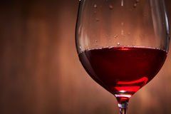 Elegant and fragile wineglass of tasty red wine against brown wooden background close-up. Royalty Free Stock Image