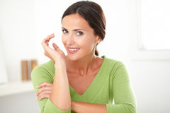 Elegant friendly girl smiling with sincerity. Elegant friendly girl in green shirt smiling with sincerity at home royalty free stock images