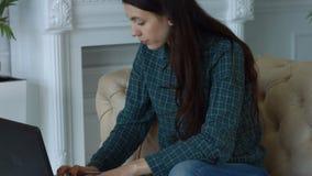 Elegant frilans- kvinna som hemma arbetar på bärbara datorn lager videofilmer