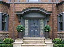 Elegant front door. With shrubbery of a large old house royalty free stock photography