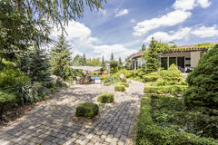 Elegant garden with the paved path. View of a garden with the paved path, plants, boxwoods and modern housefront in a sunny day Royalty Free Stock Photos