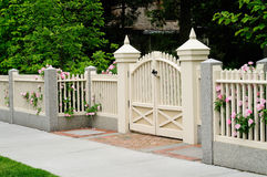 Elegant gate and fence on house entrance. Wood, granite, brick. Rose bushes coming out to sidewalk through beige, off white posts Royalty Free Stock Photos