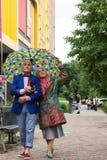 Elegant gekleed bejaard paar die onder een paraplu lopen Royalty-vrije Stock Foto's
