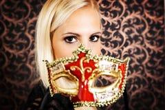 Elegant gekleed licht haarmodel die een masker dragen royalty-vrije stock fotografie